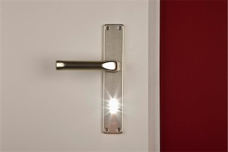 Detail of a light shining through the keyhole of a door Stock Photo - Premium Royalty-Free, Code: 653-03334583
