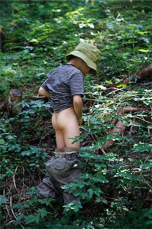 A young boy peeing in the woods Stock Photo - Premium Royalty-Free, Code: 653-03333785