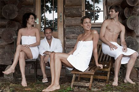 Four people relaxing outside the sauna at a health spa Stock Photo - Premium Royalty-Free, Code: 653-03333825