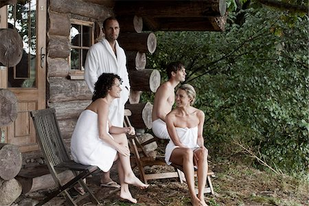 Four people relaxing outside the sauna at a health spa Stock Photo - Premium Royalty-Free, Code: 653-03333859