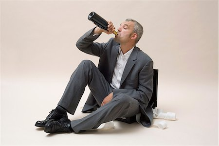 A businessman drinking a bottle of wine Stock Photo - Premium Royalty-Free, Code: 653-03333865