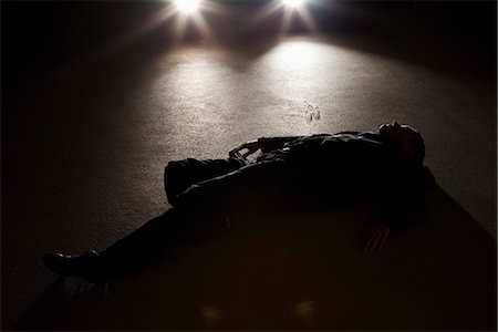 dangerous accident - A man lying on the ground in front of a car at night Stock Photo - Premium Royalty-Free, Code: 653-03459221
