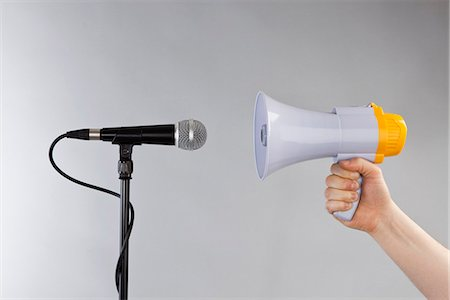 A hand holding a megaphone to a microphone Stock Photo - Premium Royalty-Free, Code: 653-03459222