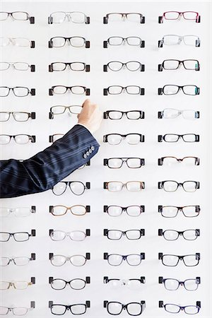 selecting - A human hand choosing a pair of glasses in an eyewear store Stock Photo - Premium Royalty-Free, Code: 653-03459533