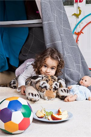 A young girl playing with a stuffed animal in a fort Stock Photo - Premium Royalty-Free, Code: 653-03459549