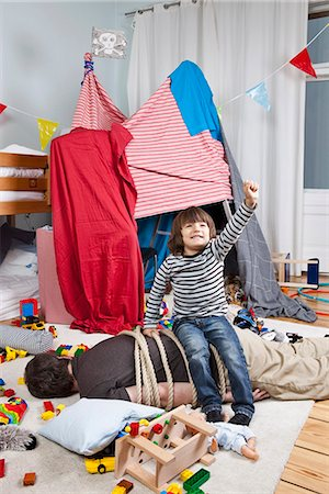 A young boy sitting on a tied up man in a child's playroom Stock Photo - Premium Royalty-Free, Code: 653-03459560