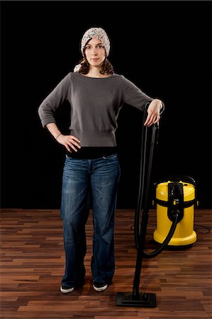 A Woman Standing Next To A Vacuum Cleaner Stock Photo - Premium Royalty-Free, Code: 653-03459730