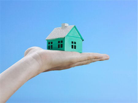 A woman holding a small house on her palm, focus on the hand Stock Photo - Premium Royalty-Free, Code: 653-03459785