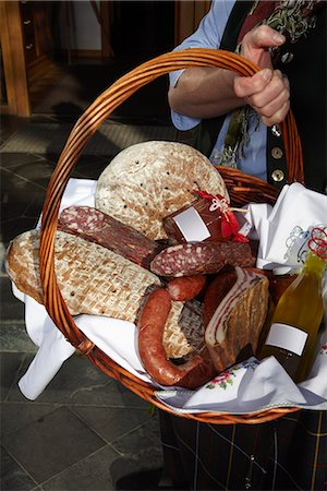 A woman holding a basket of sausages and bread, focus on basket, Carinthia, Austria Stock Photo - Premium Royalty-Free, Code: 653-03459788