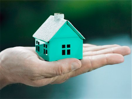 A woman holding a small house on her palm, focus on the hand Stock Photo - Premium Royalty-Free, Code: 653-03459806