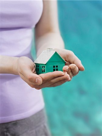 A woman holding a small house in cupped hands, focus on the hands Stock Photo - Premium Royalty-Free, Code: 653-03459823