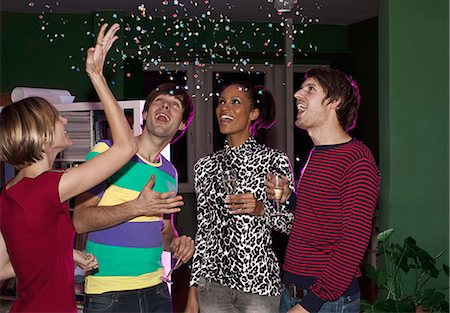 Four friends celebrating with confetti and champagne Stock Photo - Premium Royalty-Free, Code: 653-03459914