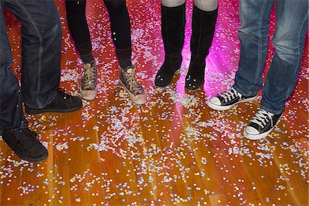 Four friends at a party with confetti, low section Stock Photo - Premium Royalty-Free, Code: 653-03459915