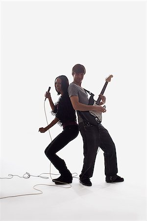 A female singer and a man playing electric guitar, studio shot, white background, back lit Stock Photo - Premium Royalty-Free, Code: 653-03459934