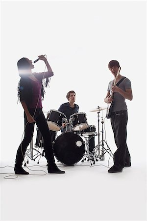 A drummer, guitarist and singer performing, studio shot, white background, back lit Stock Photo - Premium Royalty-Free, Code: 653-03459940