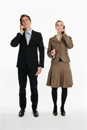 phone cord - Two business people using phone receivers connected with the same cord Stock Photo - Premium Royalty-Free, Code: 653-03459972