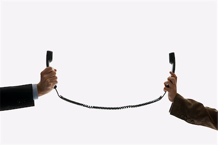 phone cord - Two business people holding telephone receivers connect with the same cord Stock Photo - Premium Royalty-Free, Code: 653-03459992