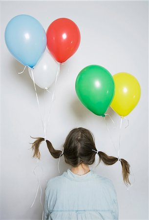 Rear view of a girl with helium balloons tied to her pigtails Stock Photo - Premium Royalty-Free, Code: 653-03575345