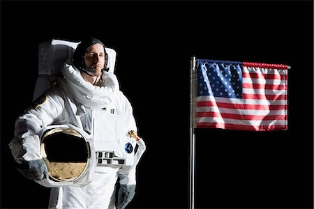 An astronaut holding his helmet standing next to an American flag, portrait Stock Photo - Premium Royalty-Free, Code: 653-03575368