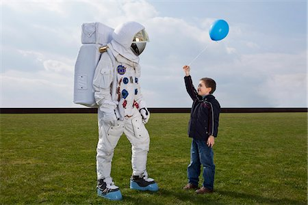 A boy holding out a balloon to an astronaut Stock Photo - Premium Royalty-Free, Code: 653-03575373