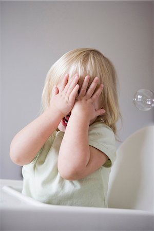 shy baby - A young girl covering her face with her hands Stock Photo - Premium Royalty-Free, Code: 653-03575727