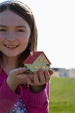 A girl holding a miniature house Stock Photo - Premium Royalty-Free, Code: 653-03575817
