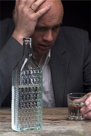 A drunk and depressed businessman holding a glass of vodka Stock Photo - Premium Royalty-Free, Code: 653-03575838