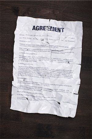 A wrinkled, torn employment agreement taped together and flattened out Stock Photo - Premium Royalty-Free, Code: 653-03575850