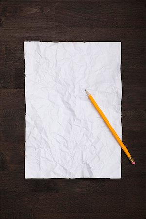 A pencil and a crumpled piece of paper flattened back out Stock Photo - Premium Royalty-Free, Code: 653-03575864