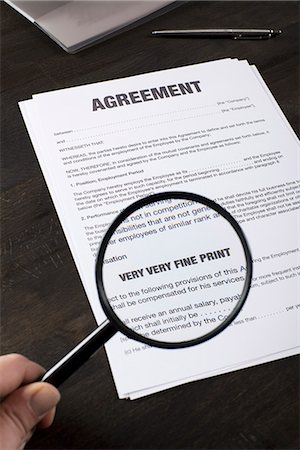 Examining the fine print of an employment agreement with a magnifying glass Stock Photo - Premium Royalty-Free, Code: 653-03575863