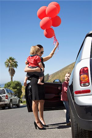 A woman holding a toddler and a bunch of balloons next to a girl getting into a car Stock Photo - Premium Royalty-Free, Code: 653-03576085