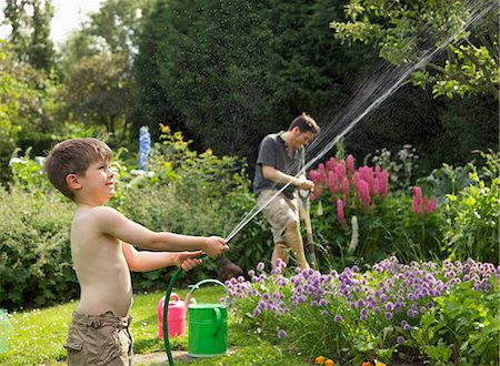 A boy squirting a hose in a garden Stock Photo - Premium Royalty-Free, Code: 653-03576094