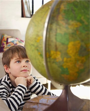 A boy looking at a world globe Stock Photo - Premium Royalty-Free, Code: 653-03576092