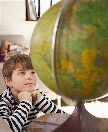 A boy looking at a world globe Stock Photo - Premium Royalty-Free, Code: 653-03576092