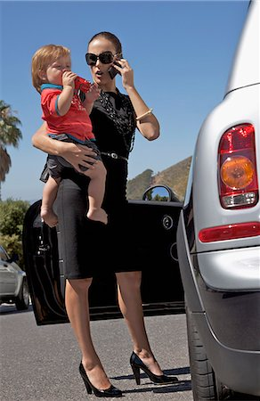 A woman holding a toddler and using a mobile phone while standing next to a car Stock Photo - Premium Royalty-Free, Code: 653-03576106