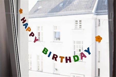 A HAPPY BIRTHDAY sign hanging in front of a window Stock Photo - Premium Royalty-Free, Code: 653-03576220