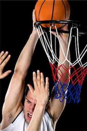 A basketball player trying to make a basket, studio shot Stock Photo - Premium Royalty-Free, Code: 653-03613081
