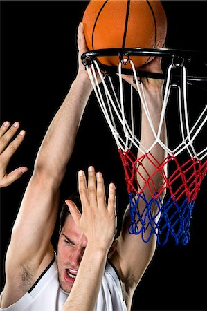 A basketball player trying to make a basket, studio shot Stock Photo - Premium Royalty-Free, Code: 653-03613081
