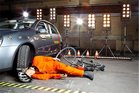 dangerous accident - A crash test dummy on ground after bicycle crashed into car Stock Photo - Premium Royalty-Free, Code: 653-03613125