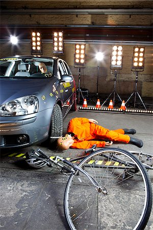dangerous accident - A crash test dummy on ground after bicycle crashed into car Stock Photo - Premium Royalty-Free, Code: 653-03613127