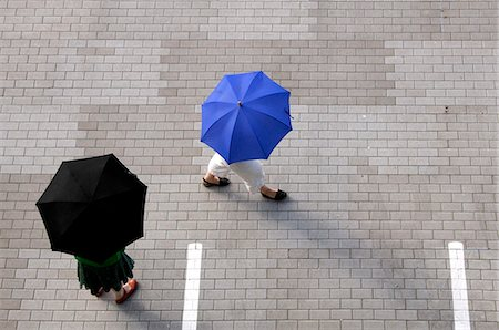 person walking on parking lot - Two women with umbrellas walking through a parking lot Stock Photo - Premium Royalty-Free, Code: 653-03613224