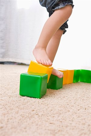 A girl balancing on top of toy blocks Stock Photo - Premium Royalty-Free, Code: 653-03705866