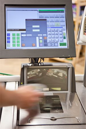 A cashier scanning groceries at a supermarket, focus on hand Stock Photo - Premium Royalty-Free, Code: 653-03706425