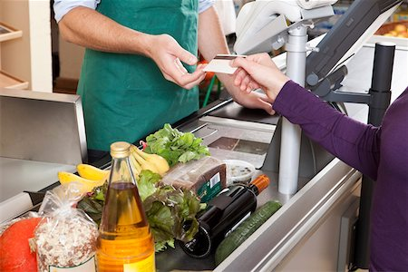 A customer handing a cashier a credit card at the supermarket Stock Photo - Premium Royalty-Free, Code: 653-03706438