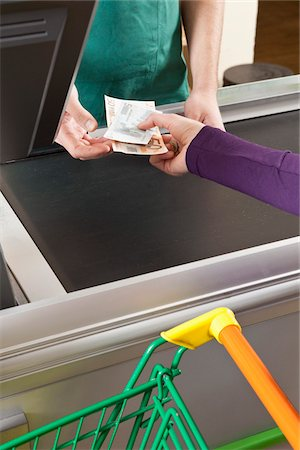 A customer handing a cashier cash at the supermarket Stock Photo - Premium Royalty-Free, Code: 653-03706458