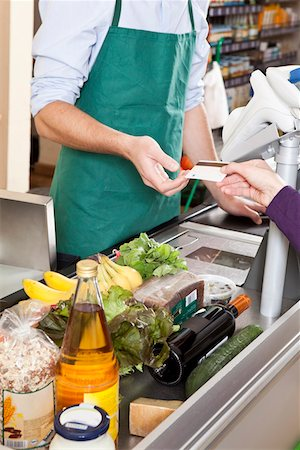 A customer handing a cashier a credit card at the supermarket Stock Photo - Premium Royalty-Free, Code: 653-03706490