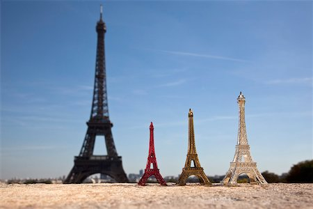 Three Eiffel Tower replica souvenirs next to the real Eiffel Tower, focus on foreground Stock Photo - Premium Royalty-Free, Code: 653-03706543