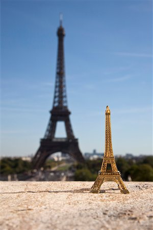 One Eiffel Tower replica souvenir next to the real Eiffel Tower, focus on foreground Stock Photo - Premium Royalty-Free, Code: 653-03706564