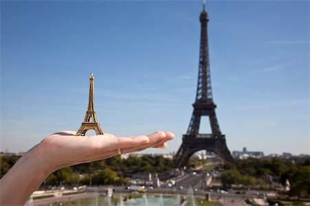 A woman holding an Eiffel Tower replica souvenir next to the real Eiffel Tower, focus on hand Stock Photo - Premium Royalty-Free, Code: 653-03706567