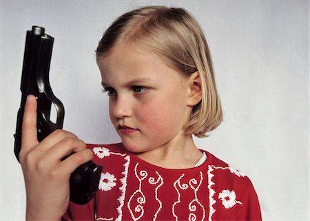 A young girl holding a gun Stock Photo - Premium Royalty-Free, Code: 653-03706739